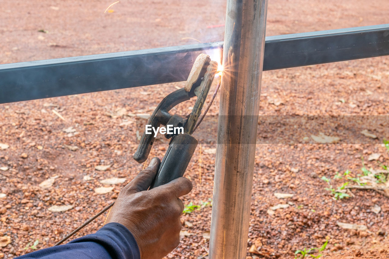Cropped Hand Of Welder Welding Metallic Fence