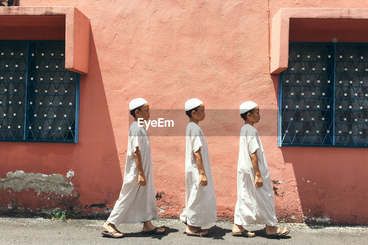 Side View Of Brothers In Traditional Clothing Walking By Building