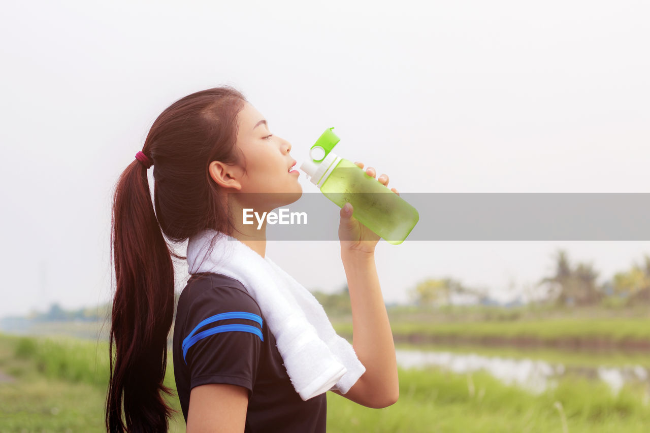 Side View Of Young Woman Drinking Water