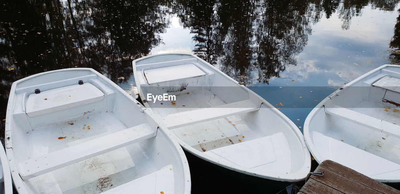 water, lake, high angle view, nature, transportation, nautical vessel, no people, mode of transportation, reflection, day, moored, outdoors, tranquility, tree, plant, white color, wood - material, travel, floating on water, rowboat