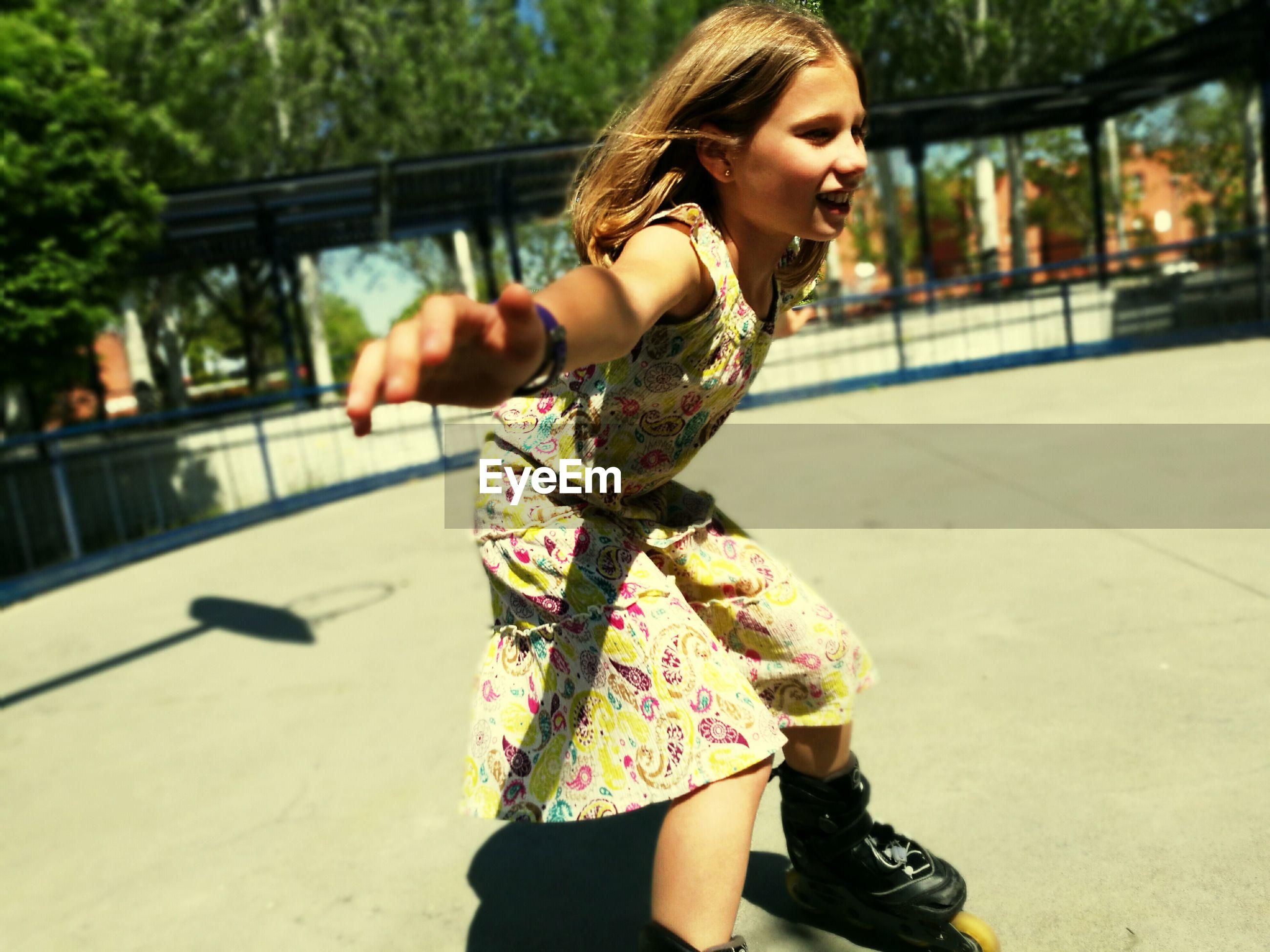 Playful girl inline skating at park