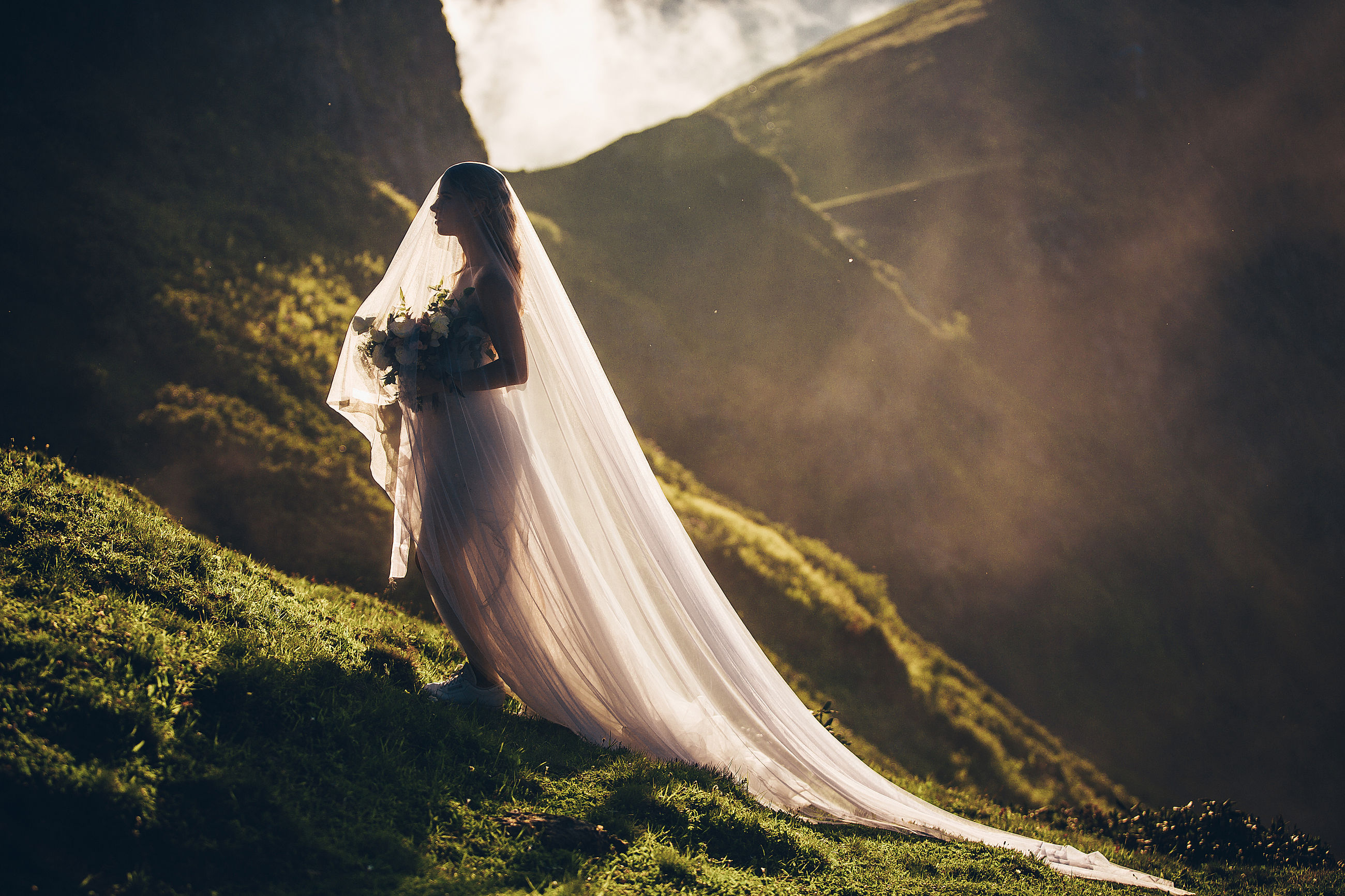 Side view of bride holding bouquet standing against mountain