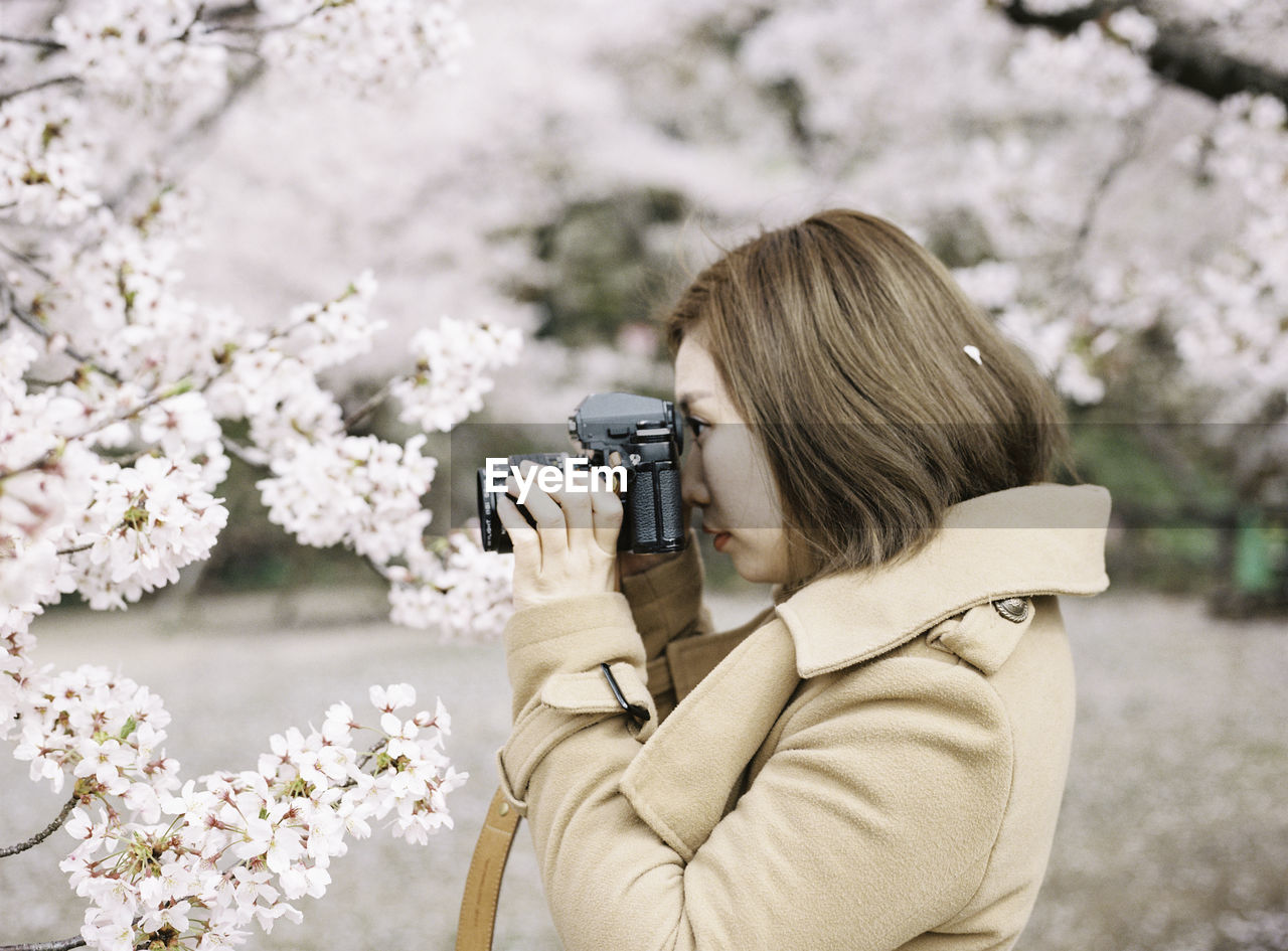 flower, young adult, flowering plant, real people, photography themes, photographing, holding, women, day, leisure activity, young women, plant, nature, one person, adult, focus on foreground, camera - photographic equipment, technology, activity, hairstyle, outdoors, digital camera, photographer