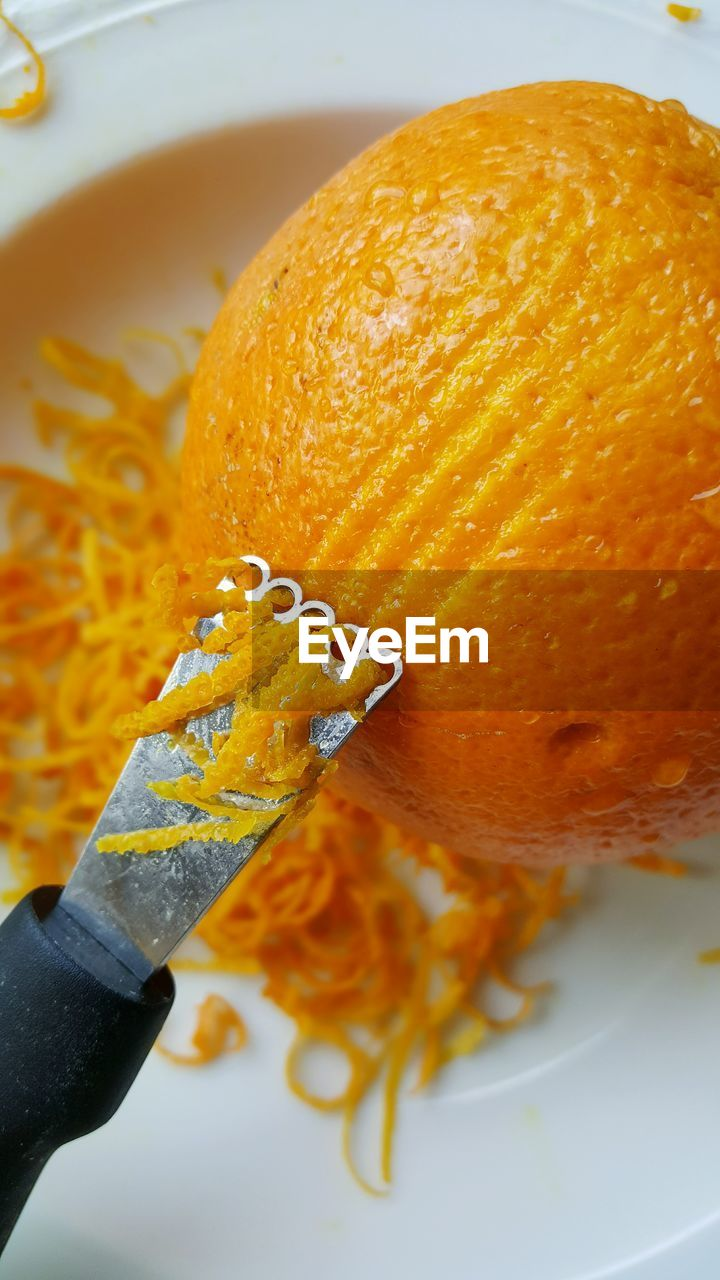 food and drink, food, human hand, orange color, freshness, close-up, one person, human body part, indoors, healthy eating, citrus fruit, plate, real people, ready-to-eat, day