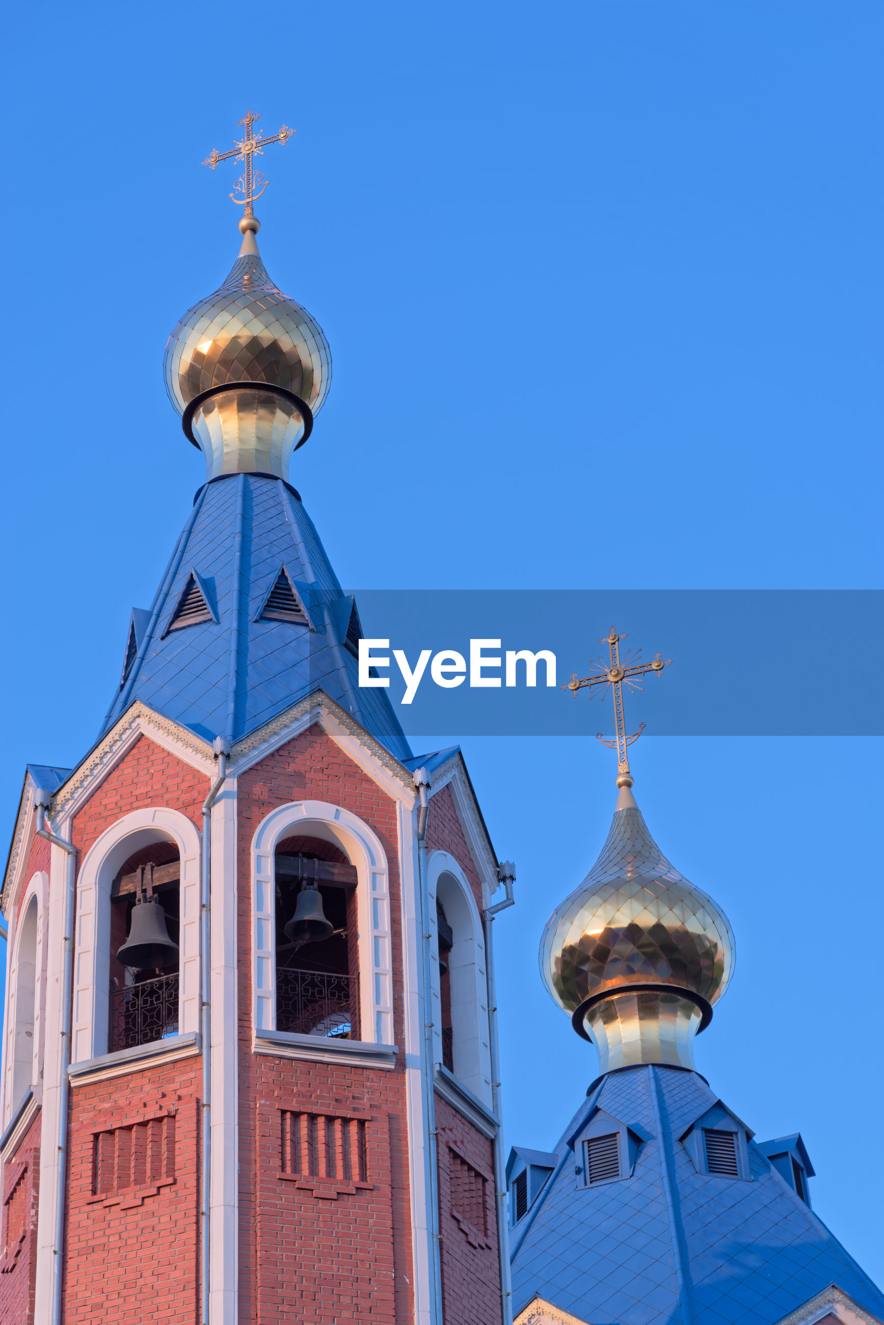 Low angle view of church roofs against clear blue sky