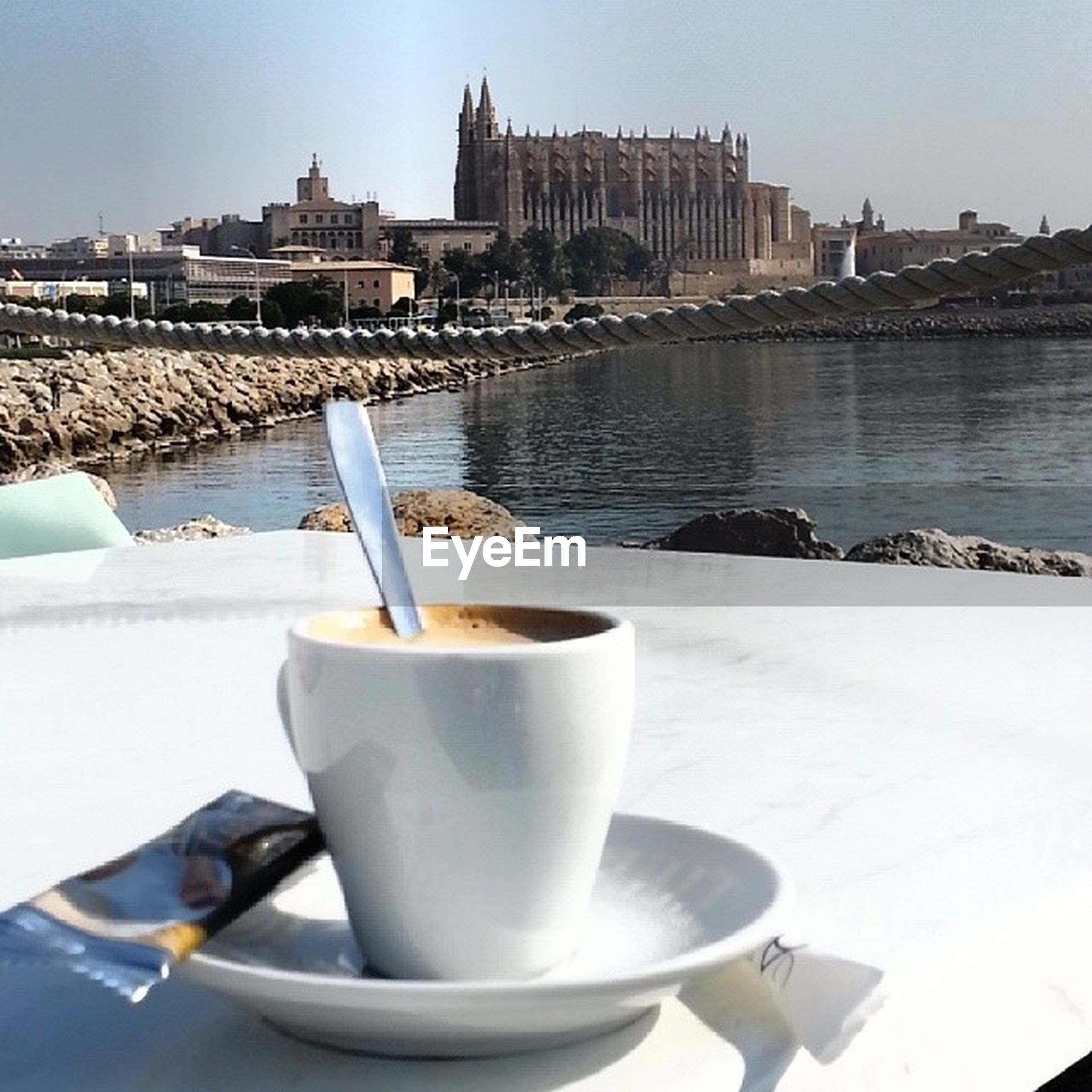 food and drink, drink, refreshment, coffee cup, water, architecture, table, built structure, saucer, building exterior, coffee - drink, close-up, white color, sky, spoon, day, sunlight, no people, cup, outdoors