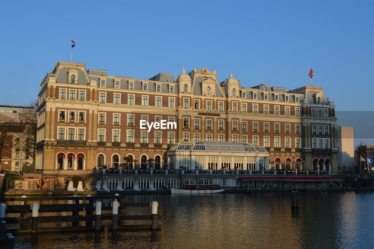 Intercontinental amstel amsterdam by river against sky