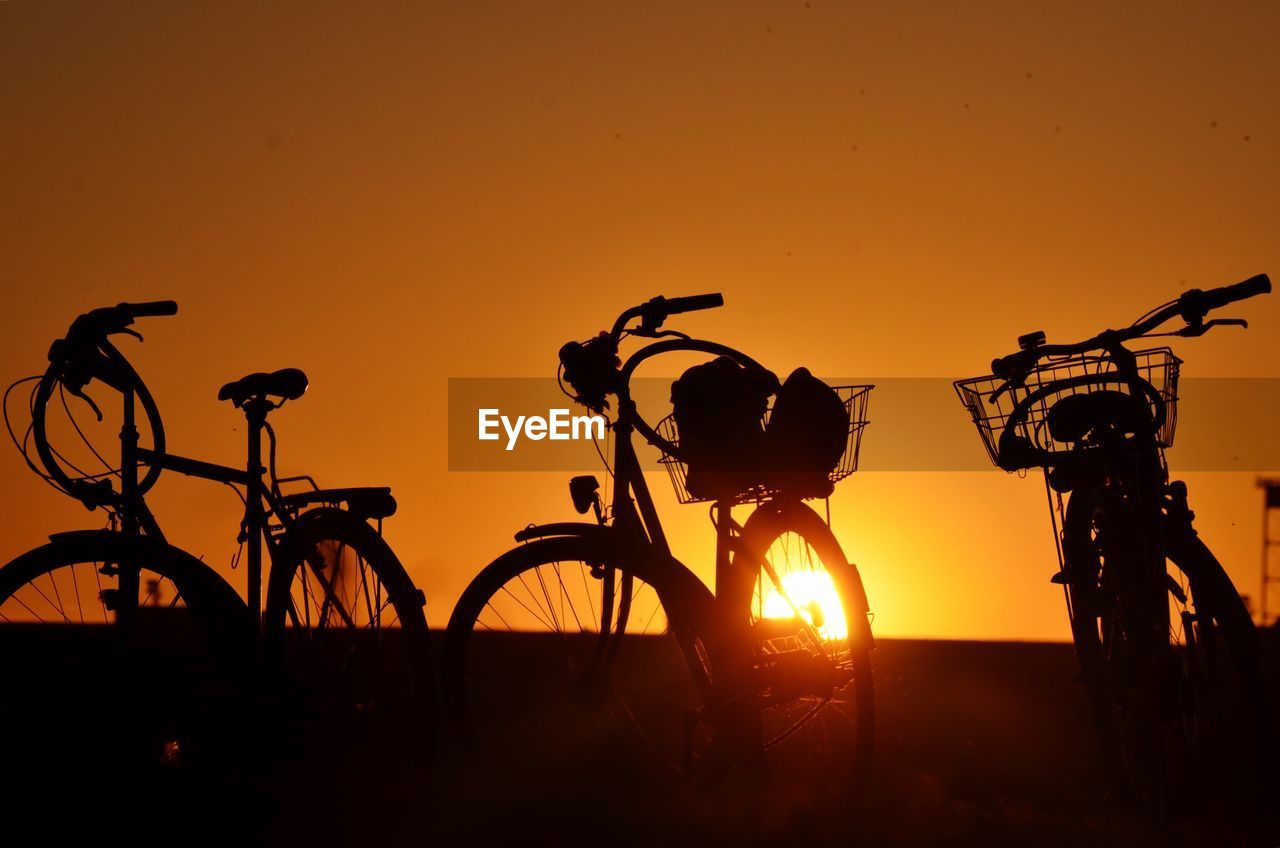 sunset, bicycle, orange color, silhouette, land vehicle, mode of transport, stationary, transportation, sun, sunlight, sky, outdoors, nature, no people, clear sky, beauty in nature, day