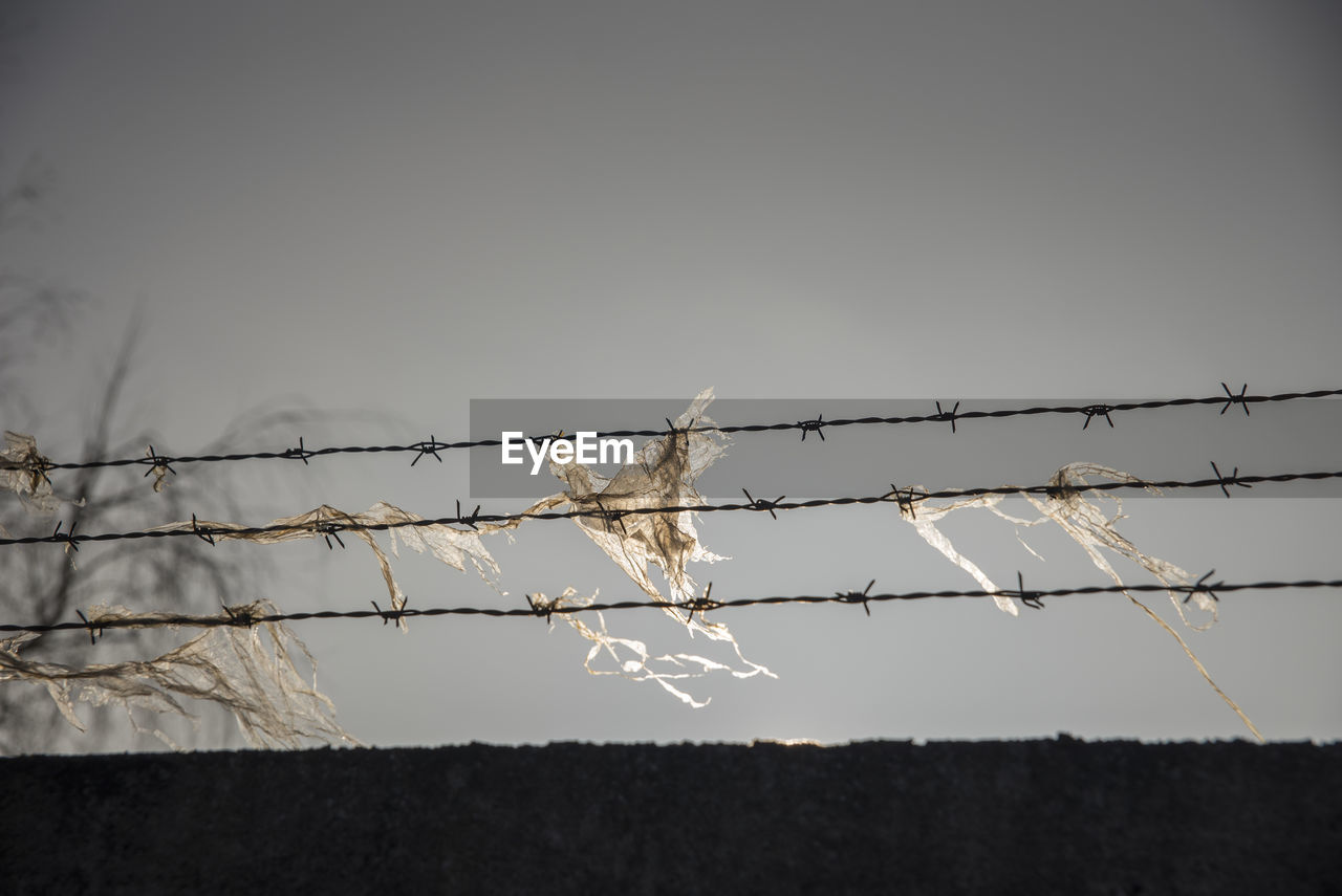 Low Angle View Of Plastic On Barbed Wire Against Clear Sky