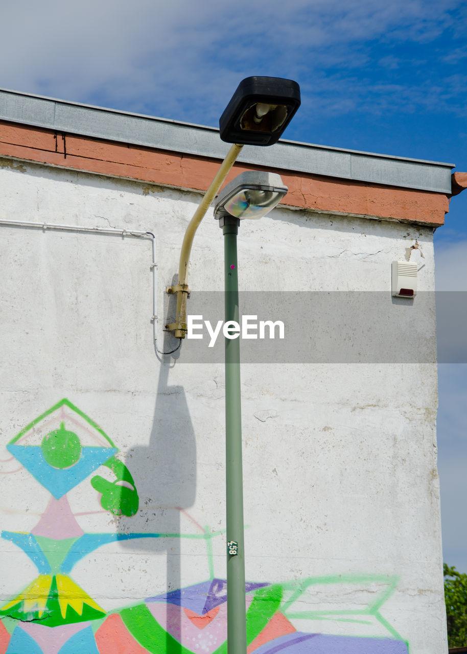 Street lights by colorful graffiti wall