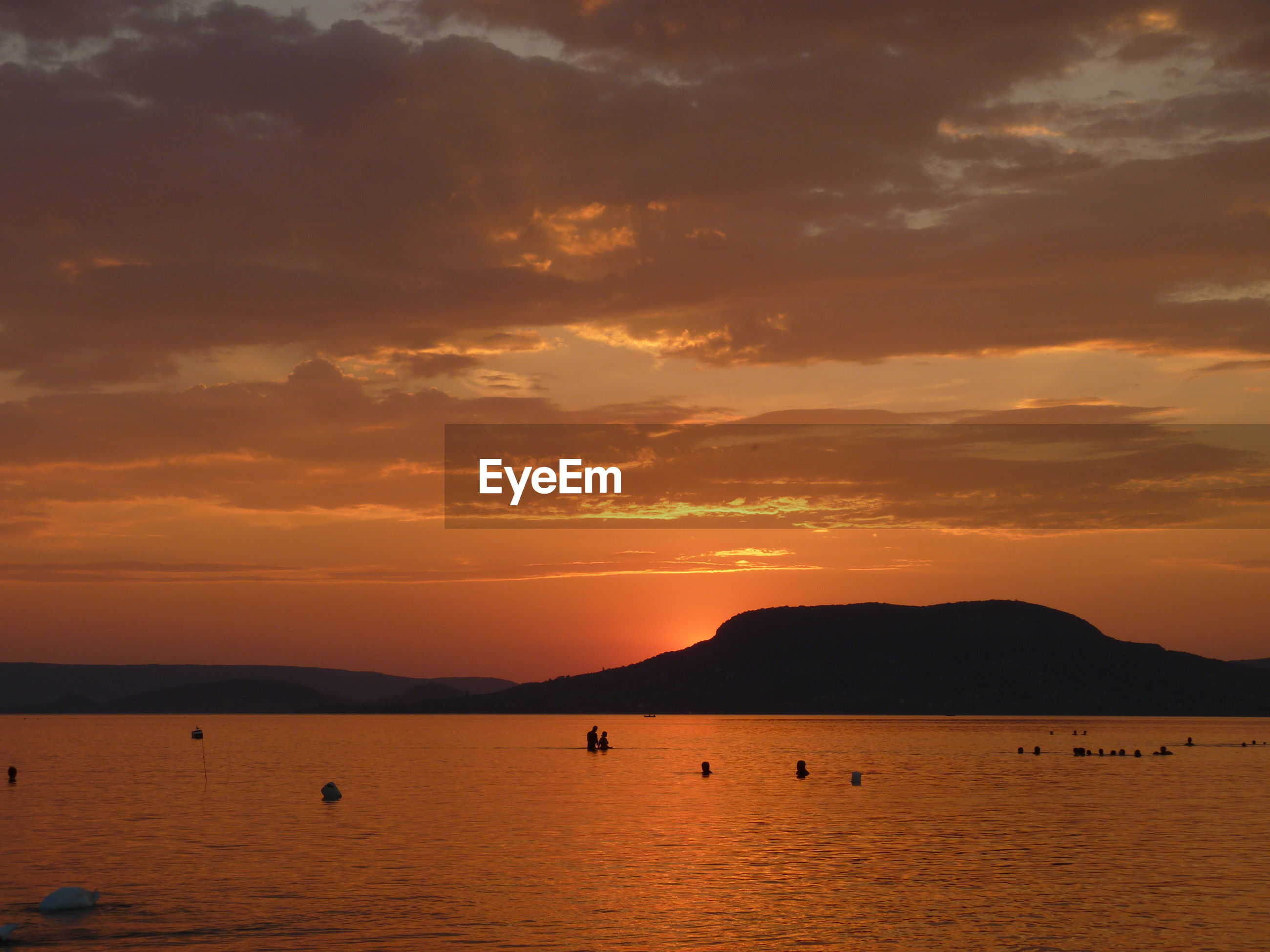 Scenic view of lake balaton against cloudy sky at sunset