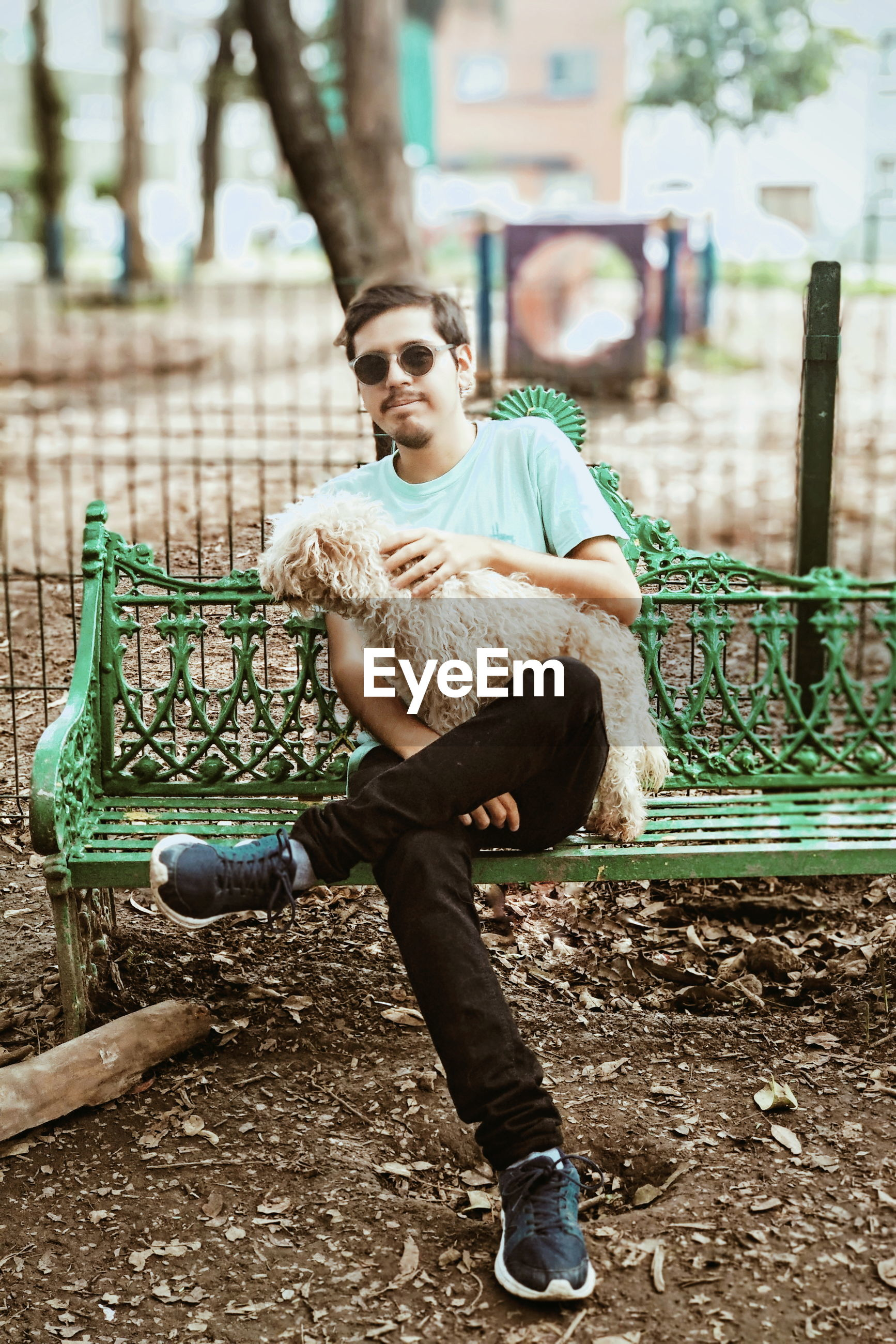 Full length of young man sitting with dog on bench