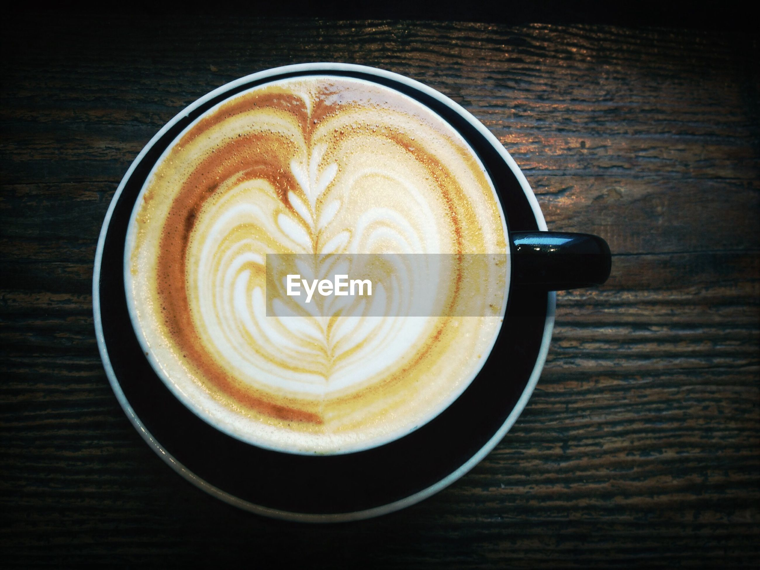 coffee cup, food and drink, table, refreshment, drink, coffee - drink, indoors, frothy drink, froth art, cappuccino, saucer, freshness, still life, coffee, close-up, directly above, latte, high angle view, wood - material, cup