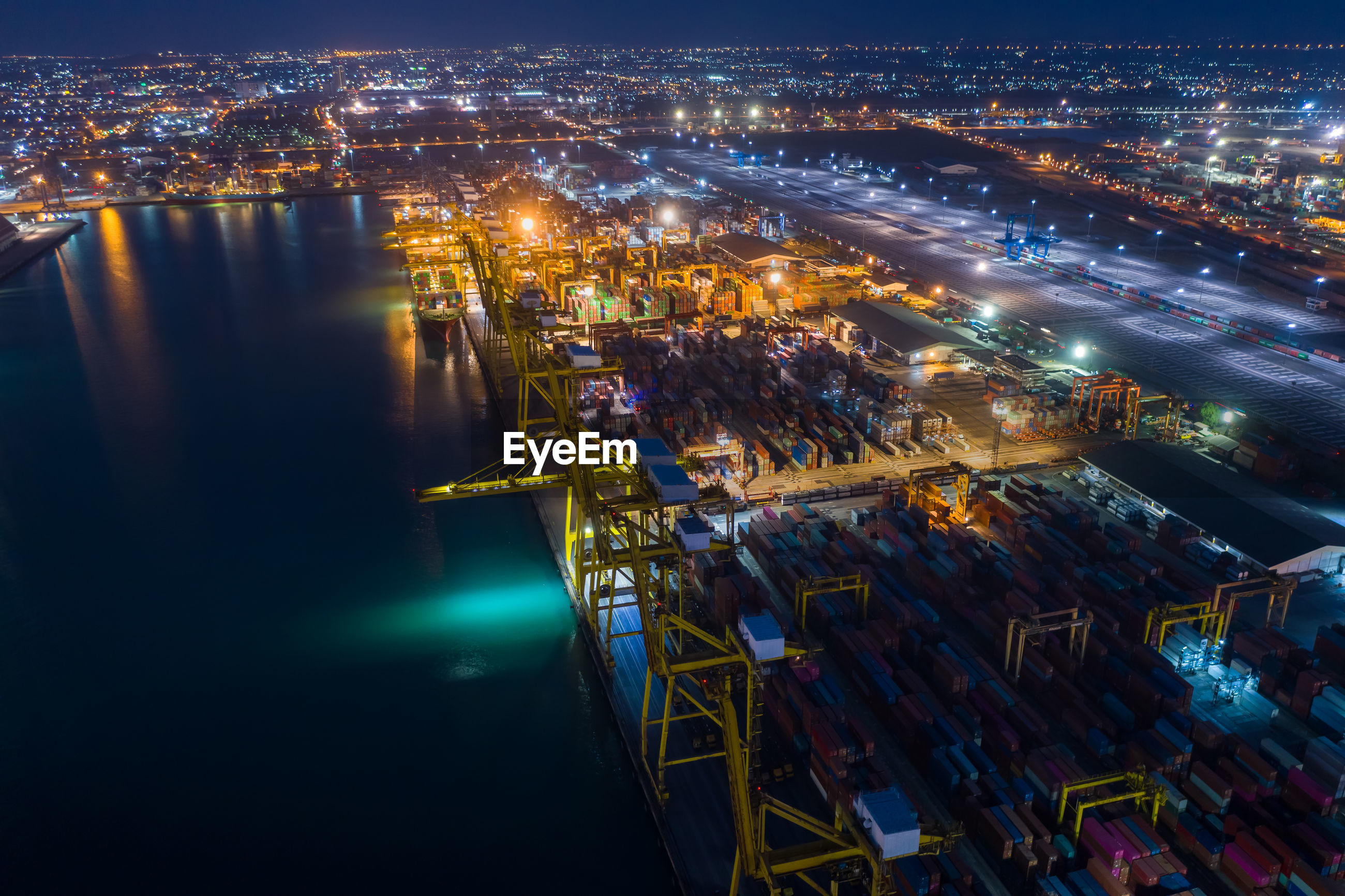 High angle view of shipping container and terminal illuminated buildings by sea at night