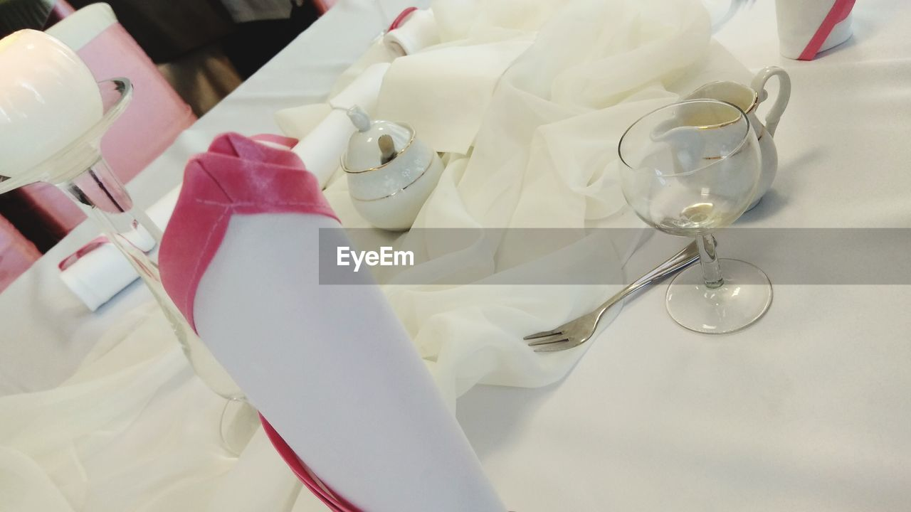 indoors, white color, no people, table, still life, high angle view, close-up, celebration, wineglass, focus on foreground, glass, eating utensil, spoon, healthcare and medicine, kitchen utensil, event, household equipment, ribbon, wedding, ribbon - sewing item