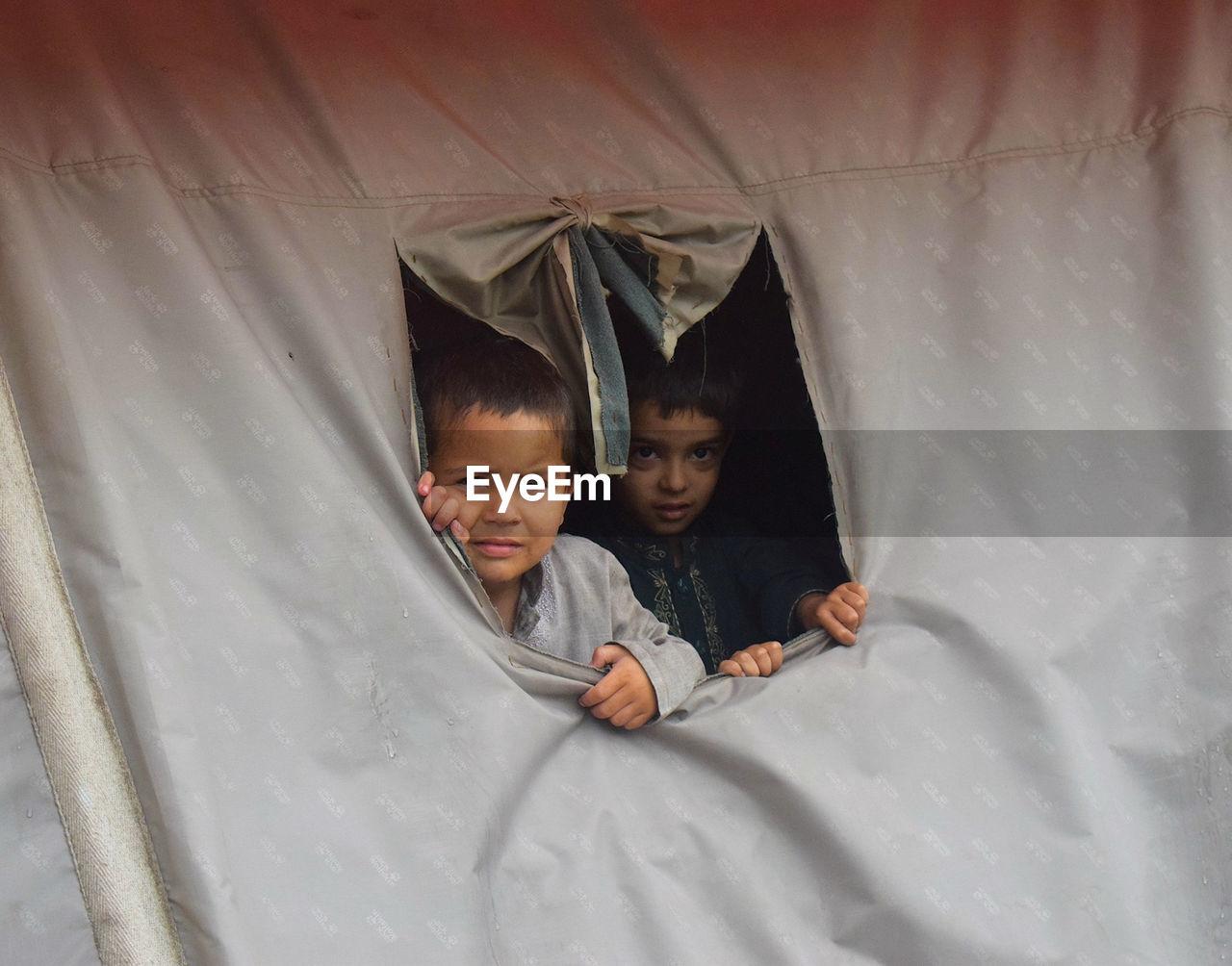 Portrait of cute boys in tent