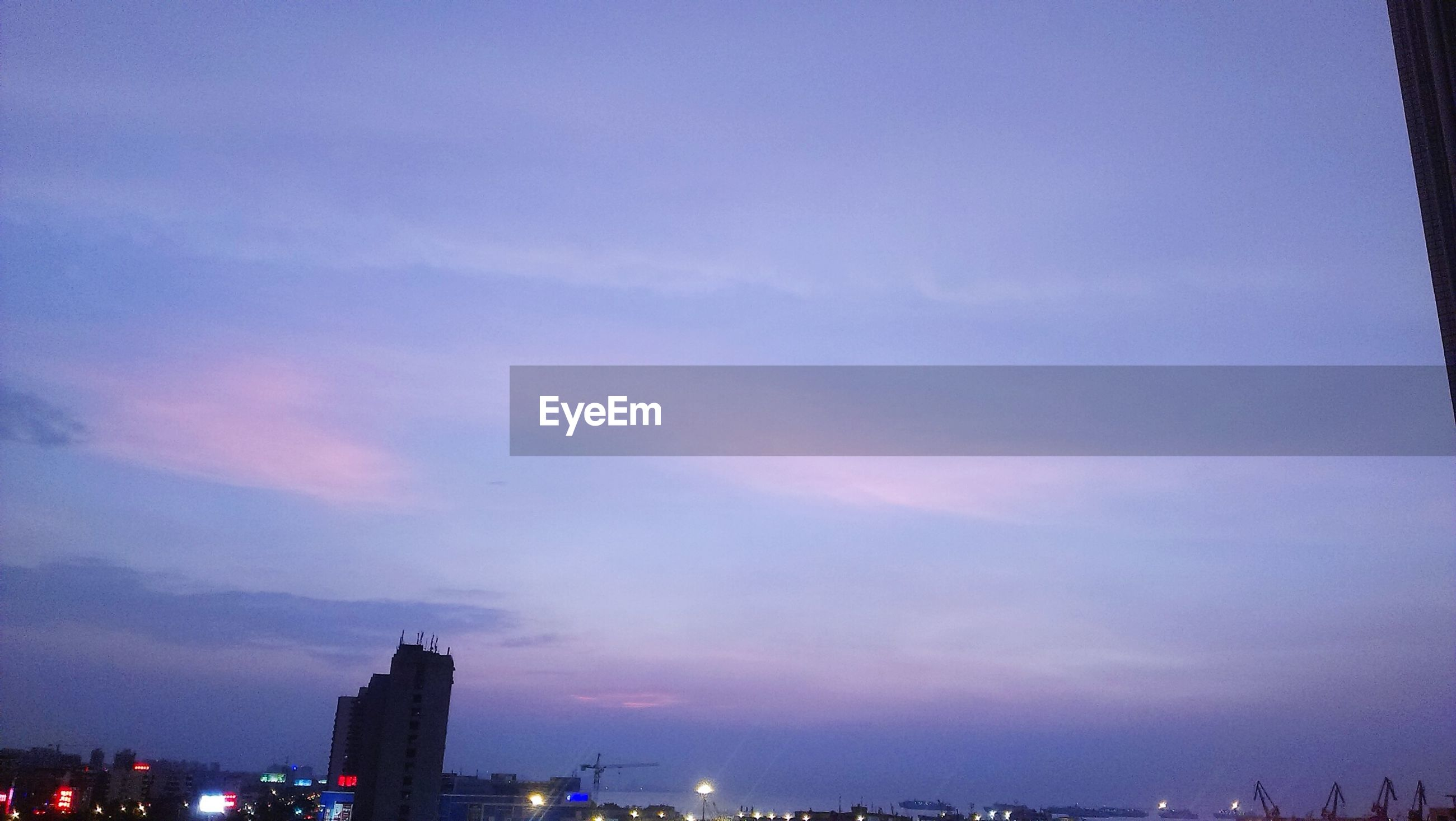 building exterior, architecture, built structure, illuminated, city, sky, cityscape, night, silhouette, dusk, cloud - sky, low angle view, residential building, outdoors, sunset, residential structure, city life, building, no people, copy space