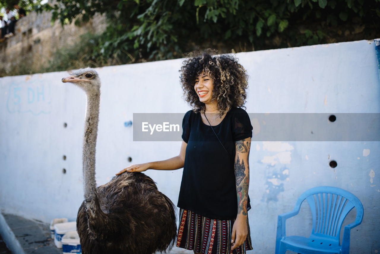 Happy woman with ostrich standing against the wall