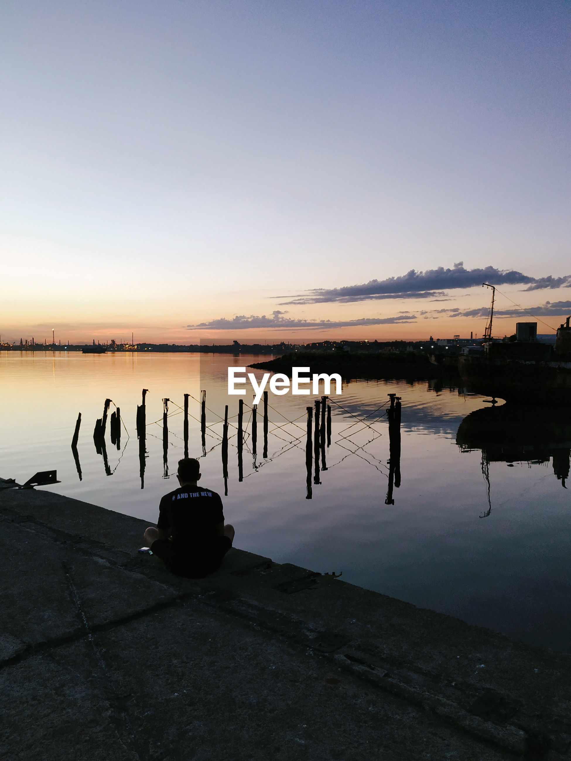 SILHOUETTE OF WOODEN POST IN LAKE AGAINST SKY DURING SUNSET
