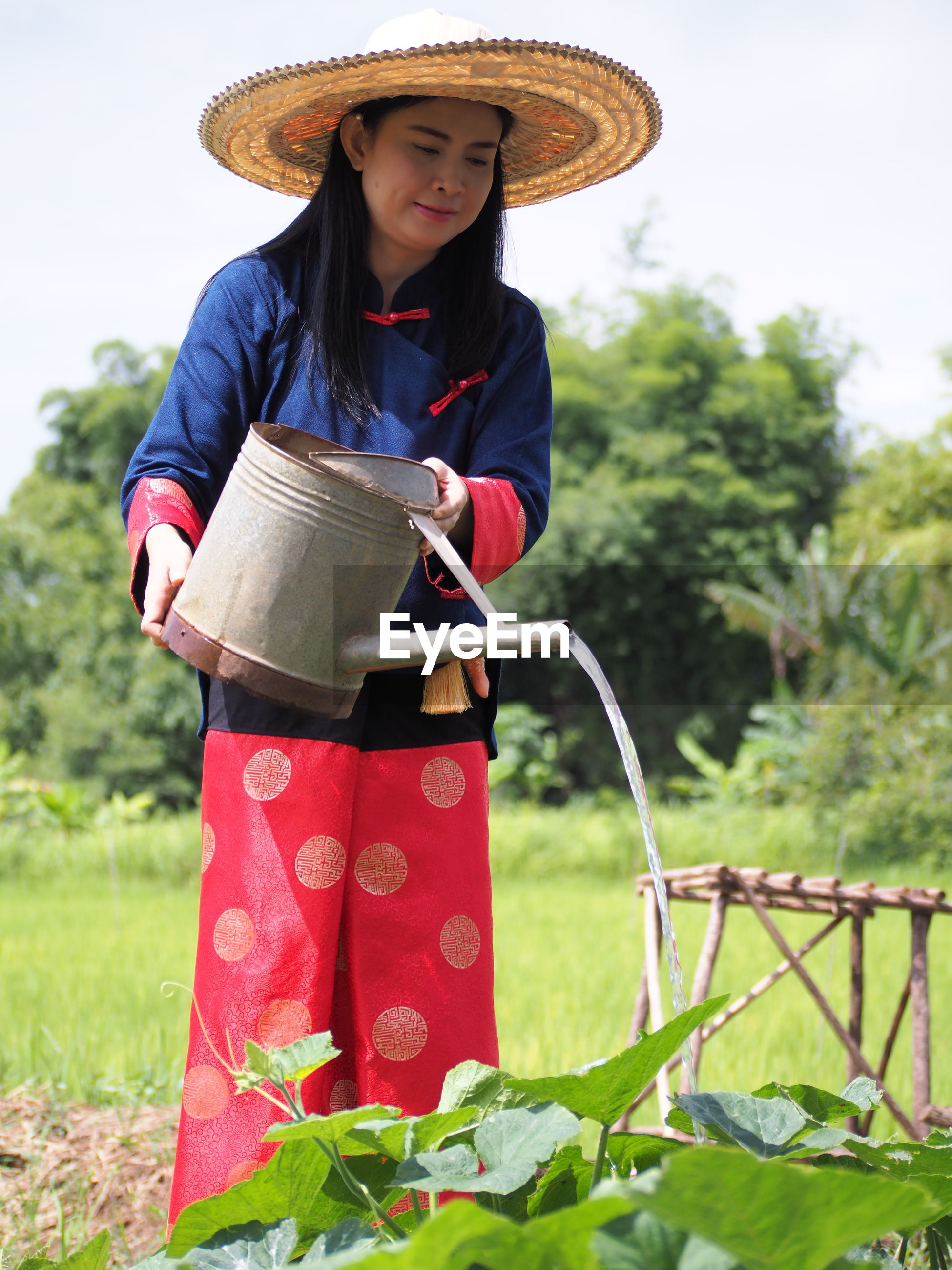 Woman watering plants while standing on field