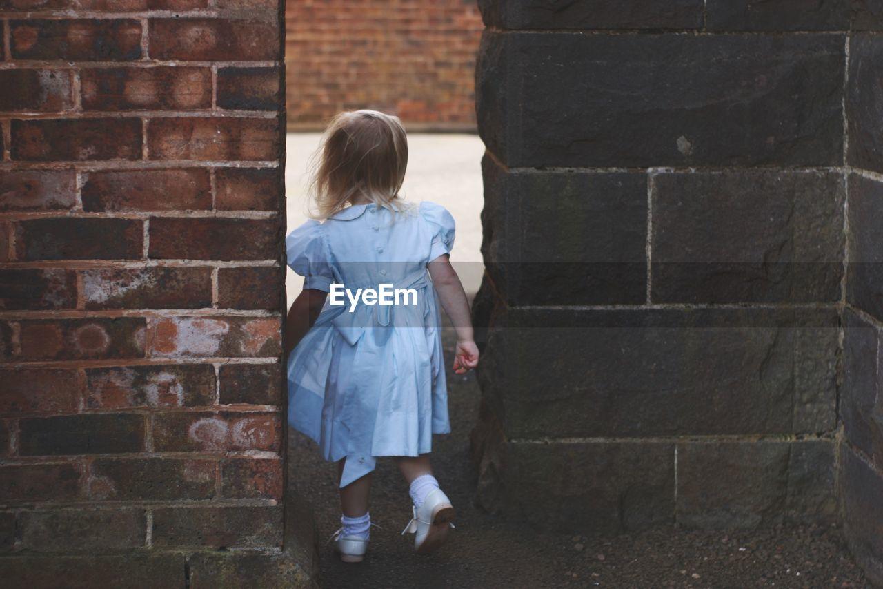 Rear view of girl walking by walls