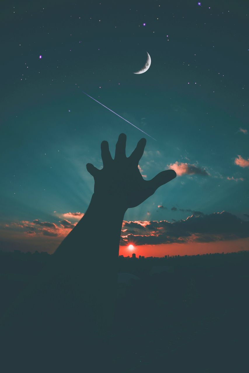 Silhouette hand gesturing towards against sky at sunset