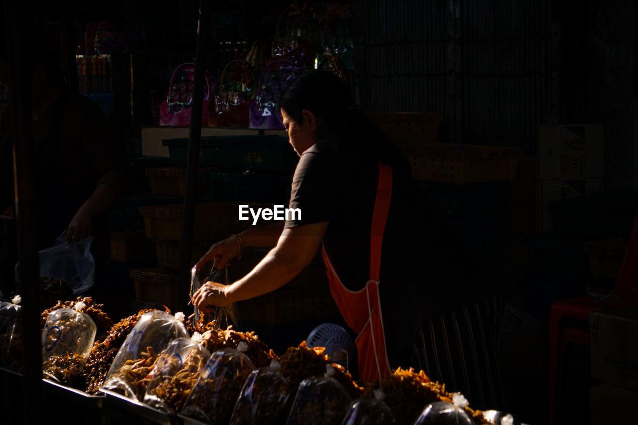 Woman working at market stall at night