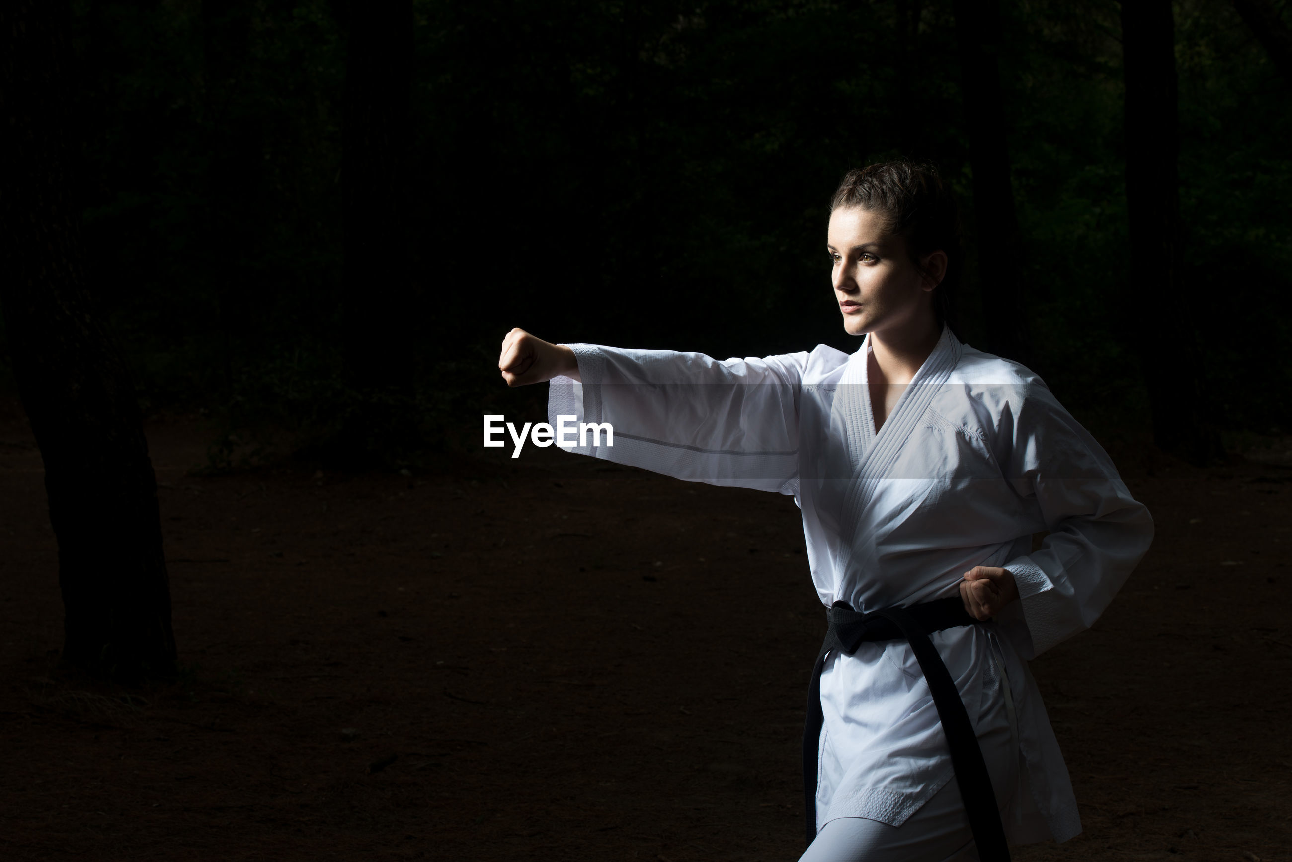 Woman practicing karate against black background