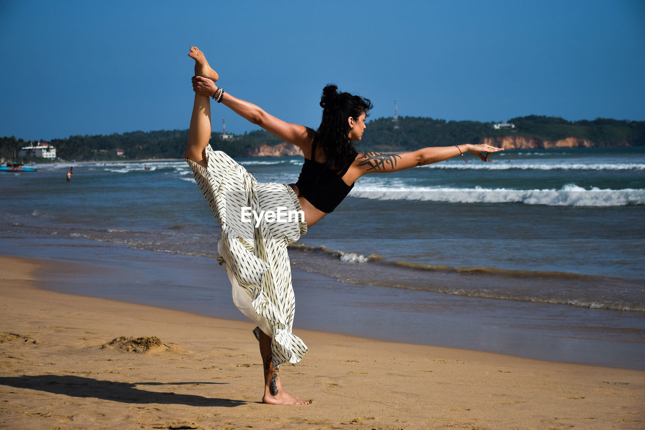beach, sea, shore, water, sand, full length, real people, one person, nature, lifestyles, balance, leisure activity, outdoors, beauty in nature, motion, day, looking at camera, vacations, young adult, scenics, wave, sky, portrait, young women, horizon over water, beautiful woman, people