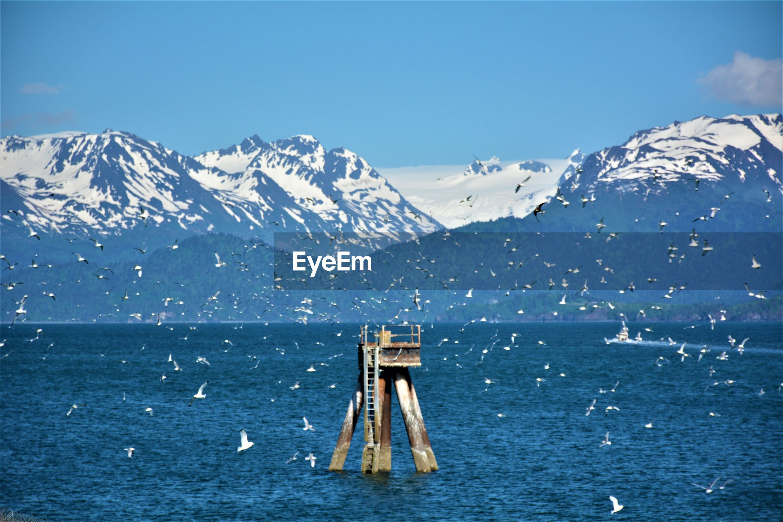 SCENIC VIEW OF SEA BY SNOWCAPPED MOUNTAINS AGAINST BLUE SKY
