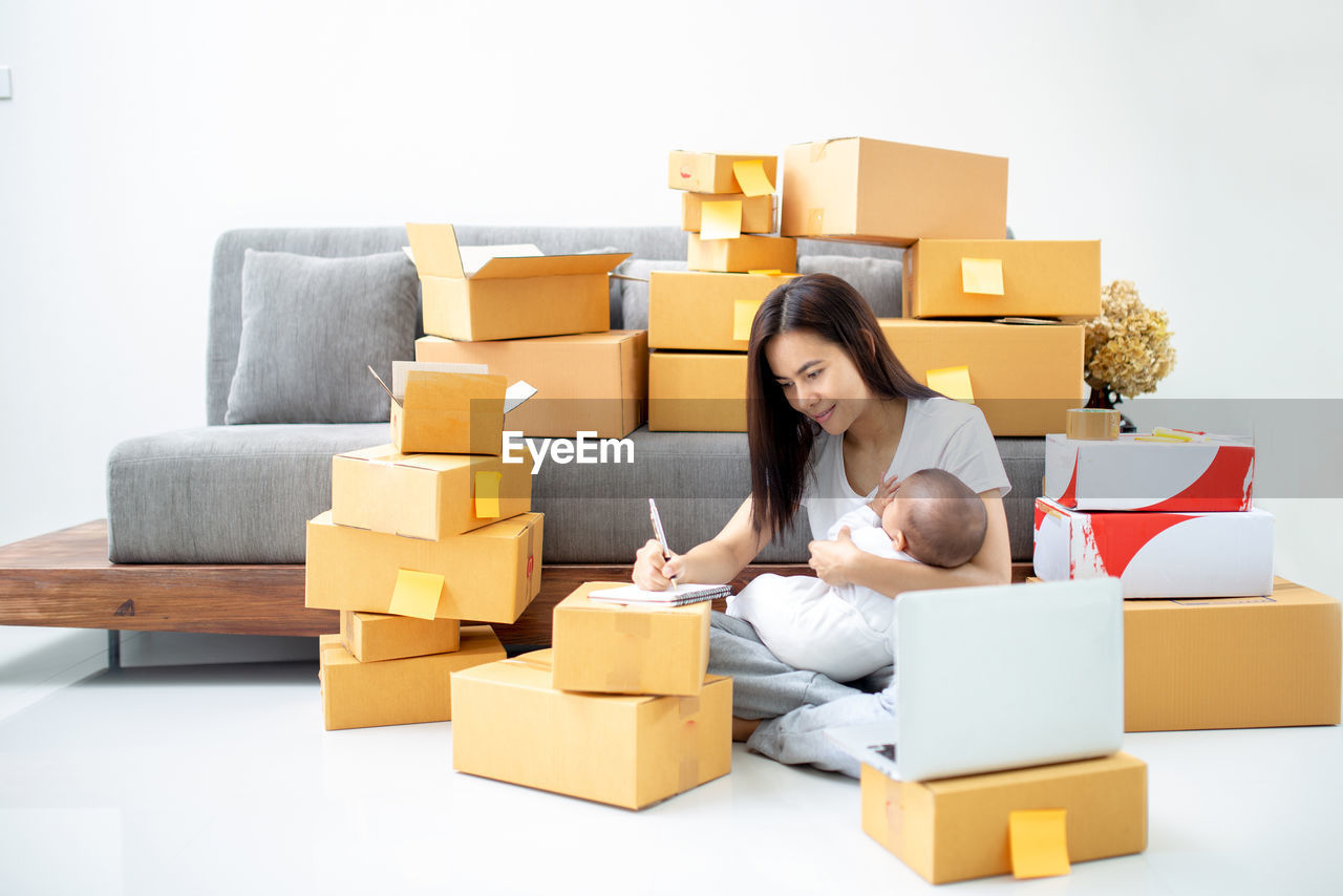 Mother with laptop and baby girl sitting on floored surrounded by cardboard box at home