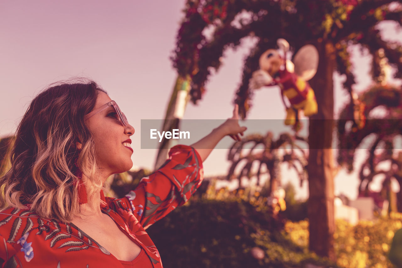 Close-Up Of Young Woman Against Trees During Sunset