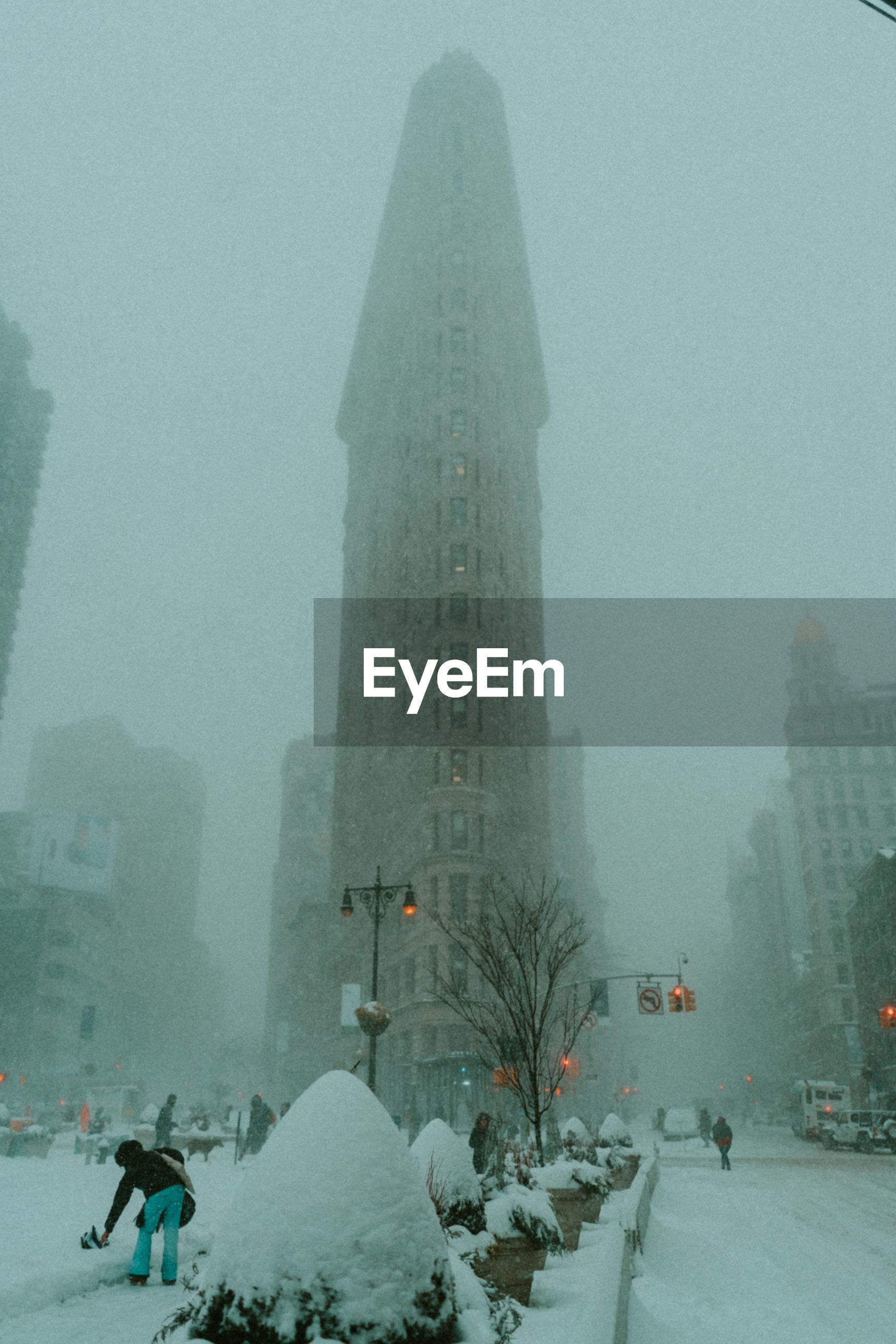 WOMAN ON SNOW COVERED CITY IN FOGGY WEATHER