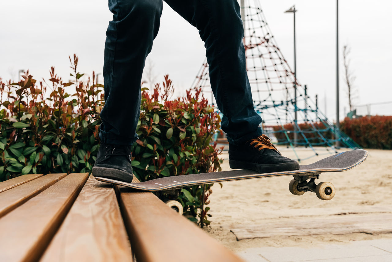 Low section of man standing on skateboard over bench