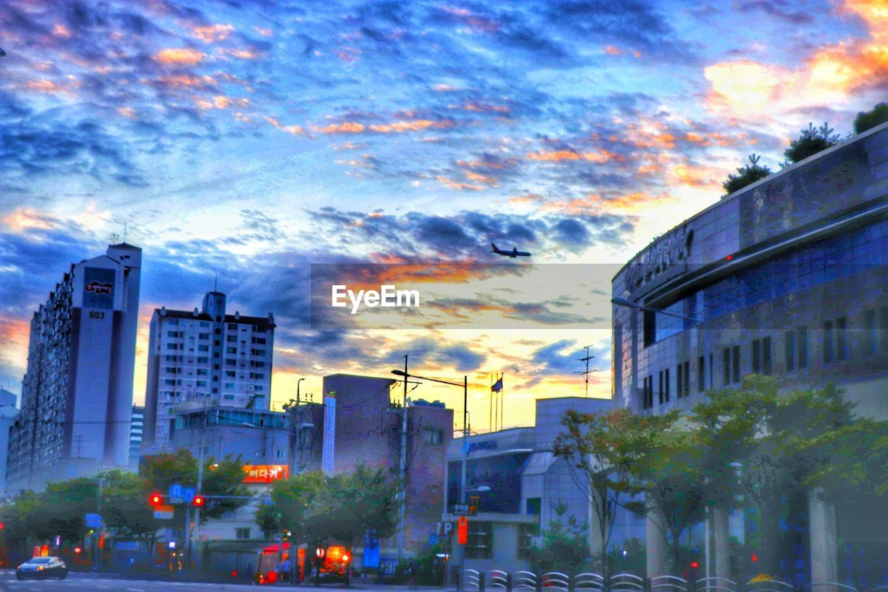 building exterior, architecture, city, built structure, sky, cloud - sky, street, outdoors, illuminated, dusk, car, skyscraper, no people, sunset, modern, cityscape, tree, day