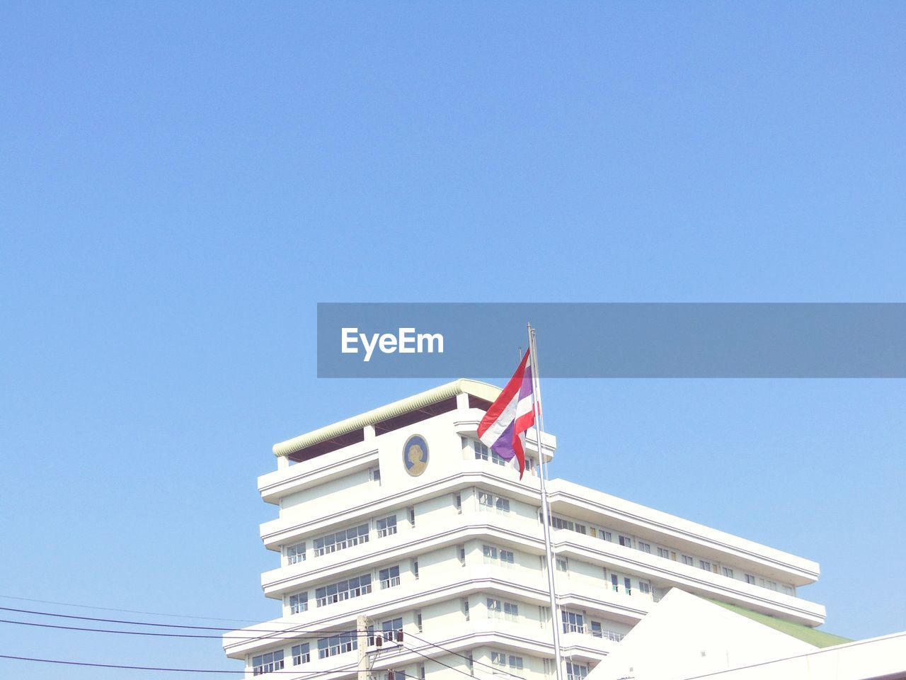 LOW ANGLE VIEW OF FLAG AGAINST BUILT STRUCTURE