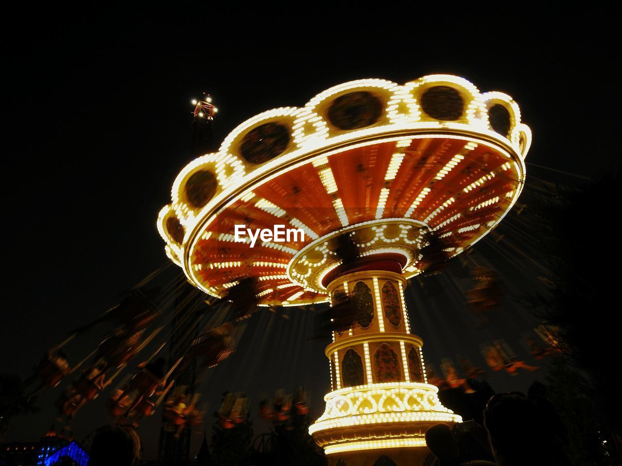 night, amusement park, arts culture and entertainment, low angle view, amusement park ride, illuminated, leisure activity, large group of people, enjoyment, outdoors, blurred motion, men, real people, motion, ferris wheel, women, clear sky, sky, carousel, people