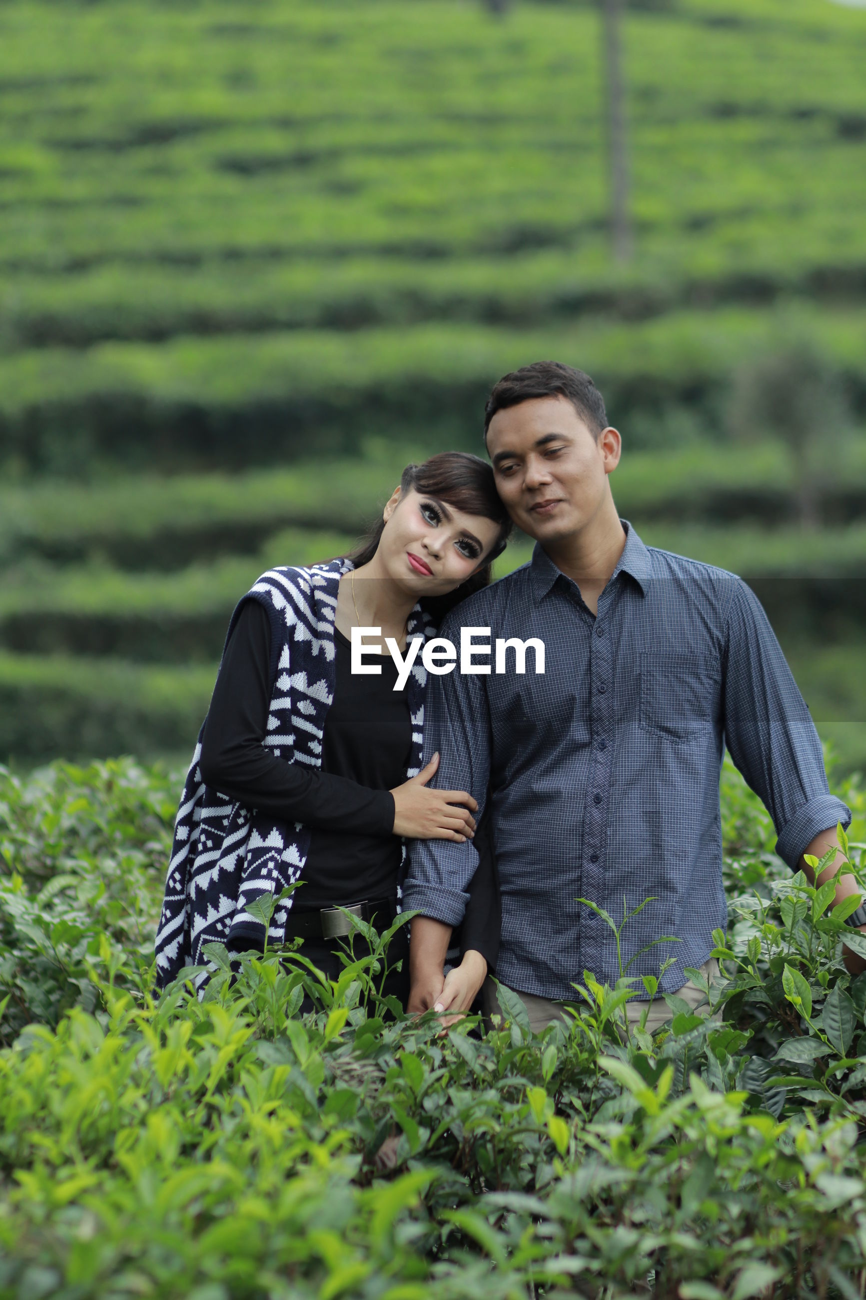 Portrait of smiling couple standing on agricultural field