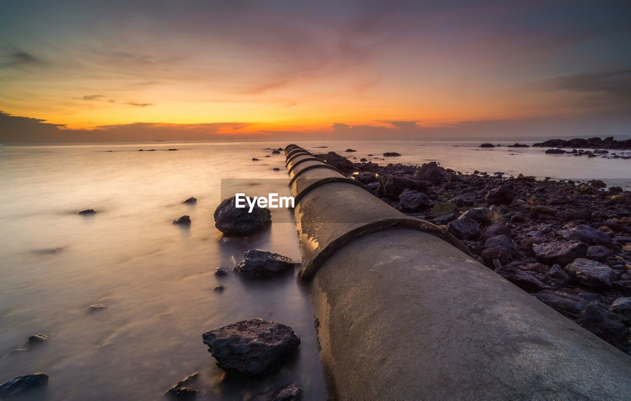 sunset, sky, water, sea, scenics - nature, beach, cloud - sky, land, orange color, beauty in nature, nature, tranquil scene, horizon over water, horizon, rock, tranquility, no people, idyllic, rock - object, outdoors, pollution
