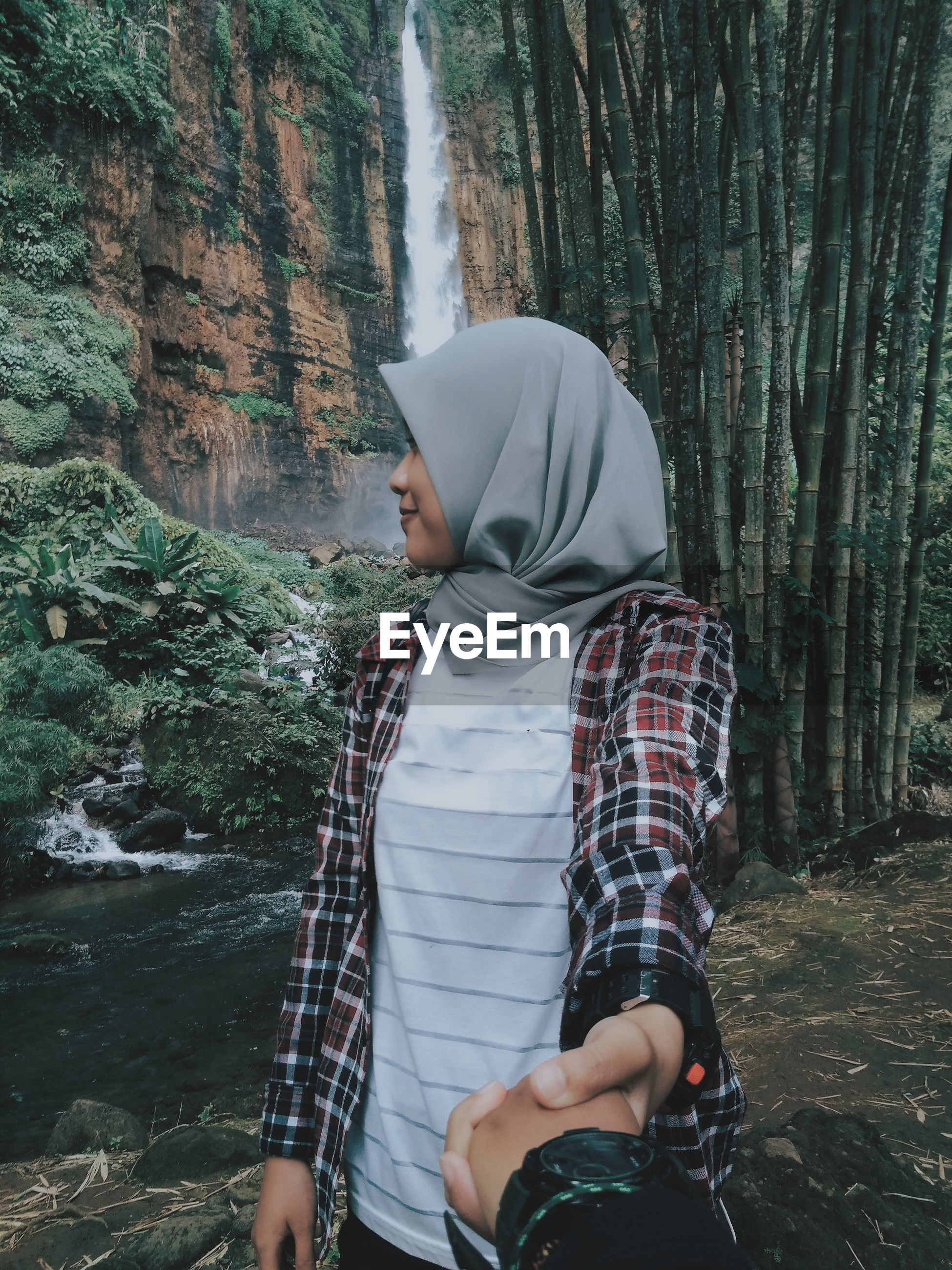 Woman holding hands of man standing against waterfall in forest