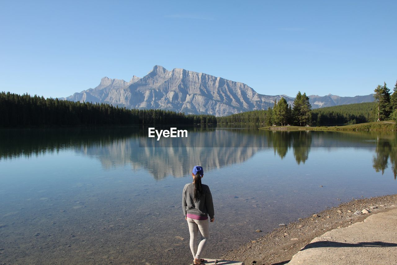 High Angle View Of Woman Standing By Calm Lake