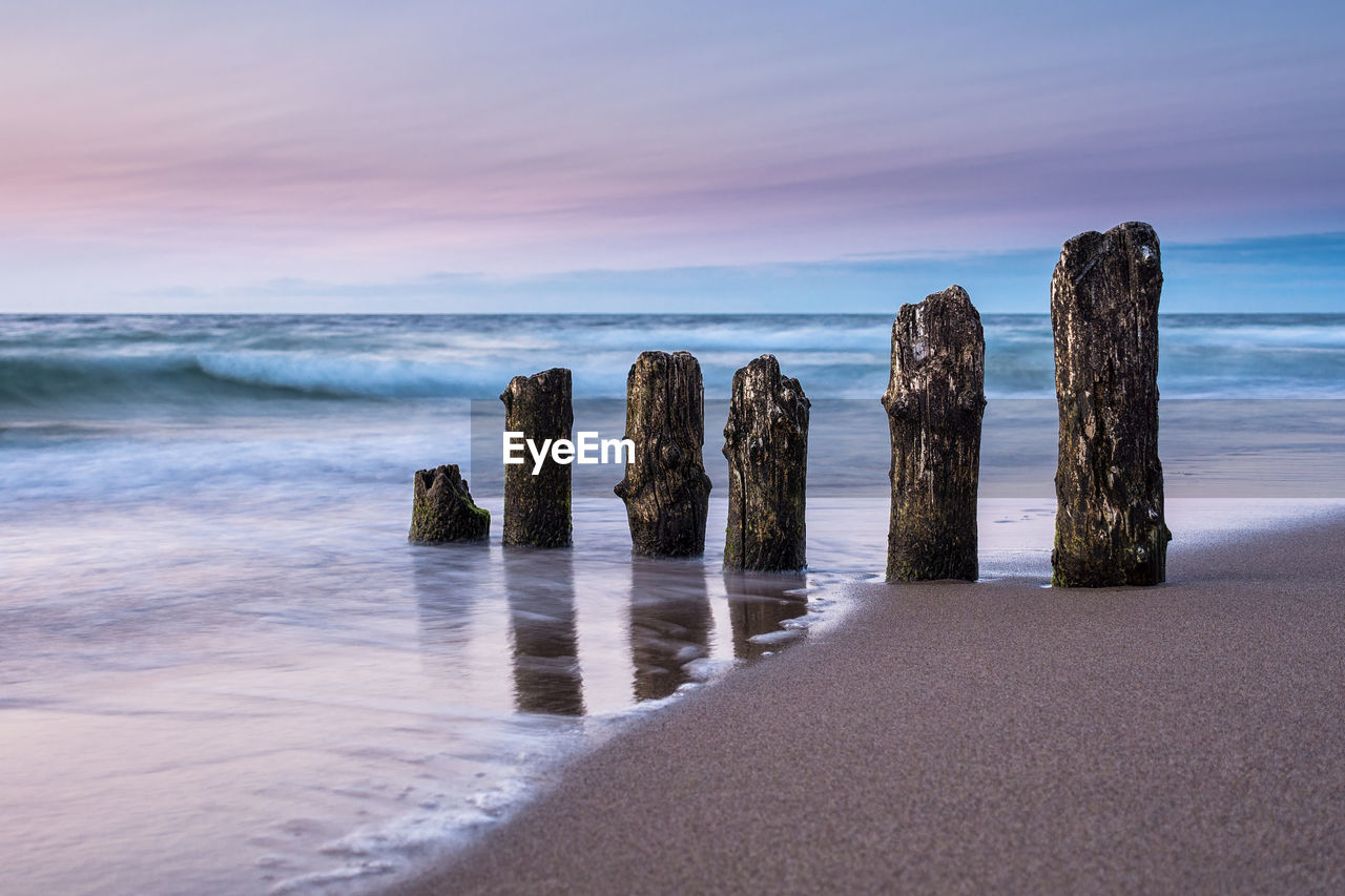 water, sea, sky, horizon over water, scenics - nature, beauty in nature, horizon, beach, tranquil scene, land, tranquility, nature, no people, idyllic, cloud - sky, sunset, wood - material, motion, wave, post, wooden post, groyne