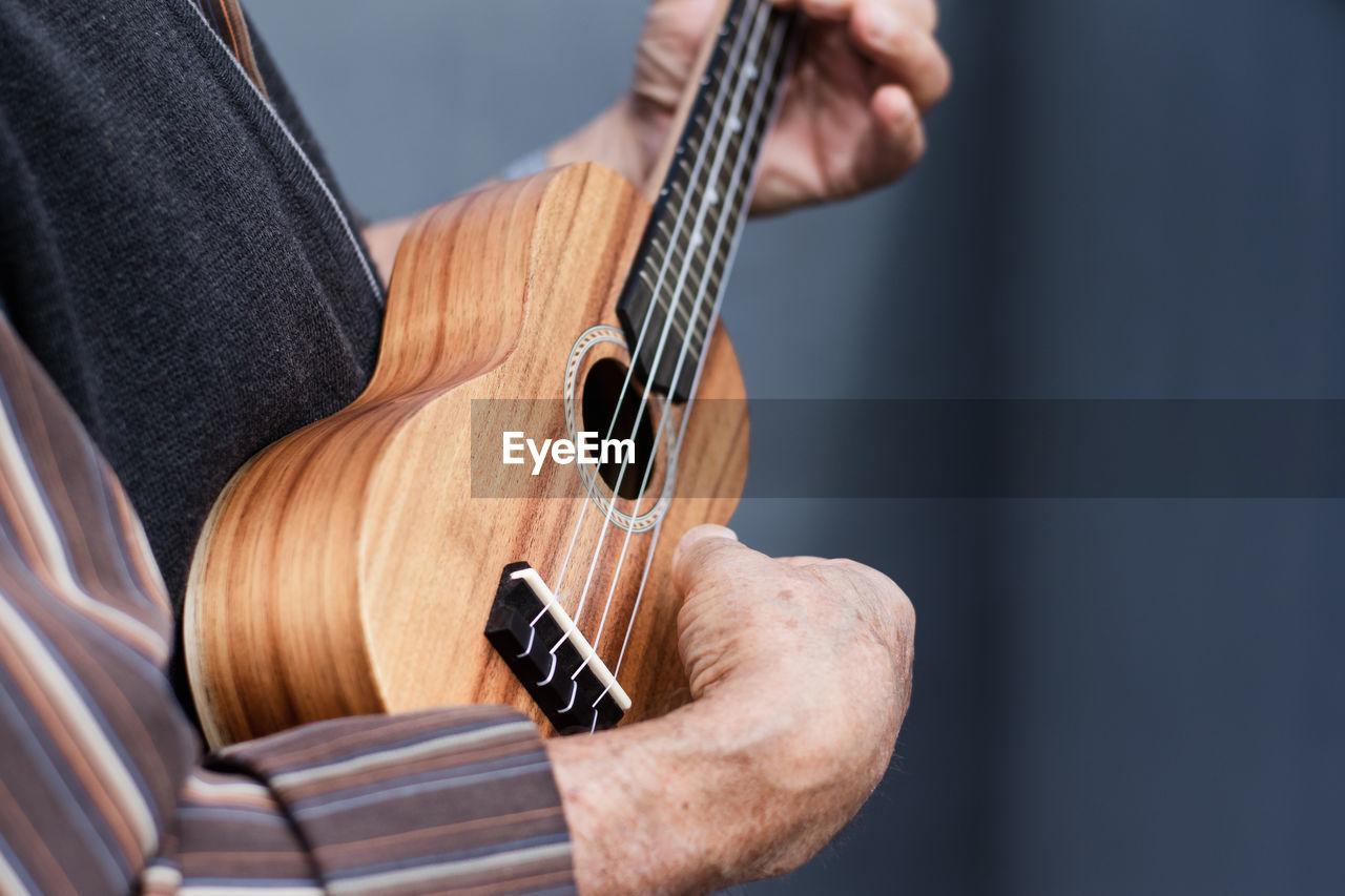 Senior person playing ukulele outdoors