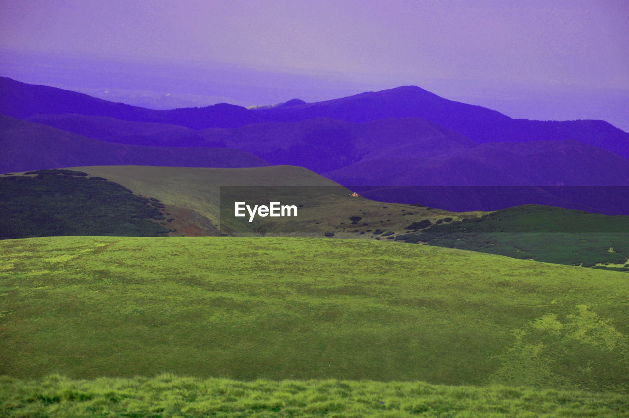 Grass Covered Mountain Ranges Against Sky