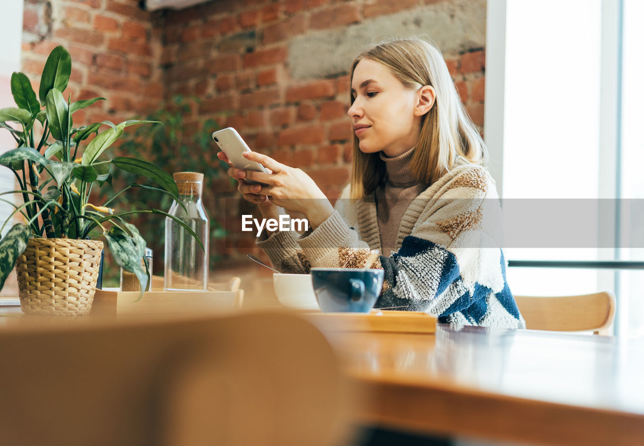Young woman using smart phone while sitting on table