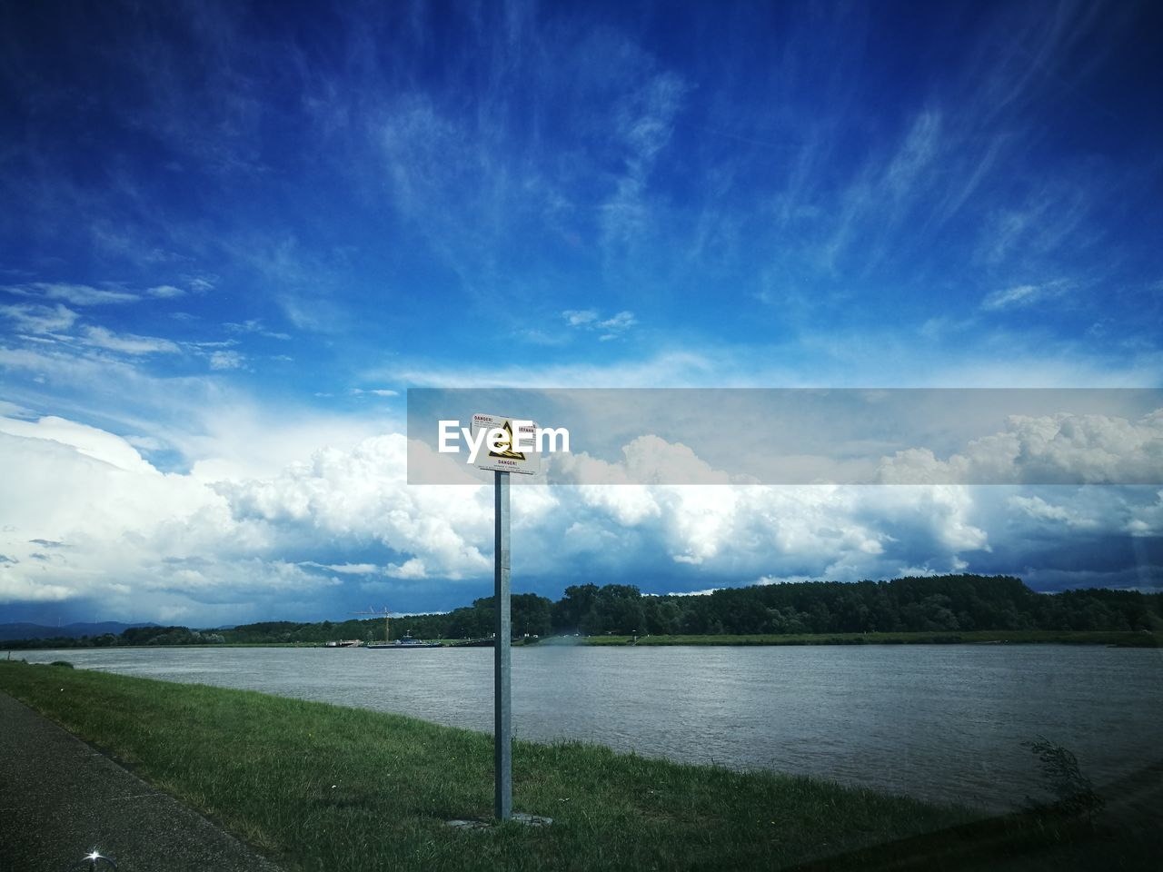 sky, tranquility, cloud - sky, tranquil scene, nature, scenics, beauty in nature, day, landscape, outdoors, no people, road, grass, road sign, blue, water
