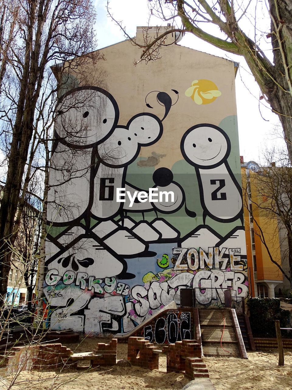 graffiti, creativity, text, built structure, architecture, communication, day, bare tree, tree, outdoors, no people, building exterior, branch