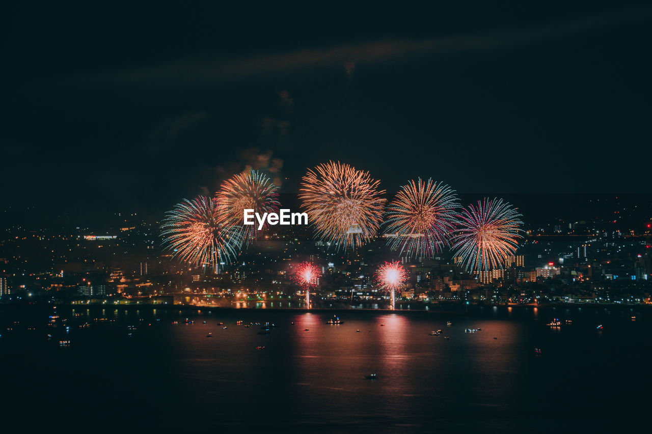 illuminated, night, firework, firework display, arts culture and entertainment, celebration, event, exploding, motion, water, glowing, long exposure, sky, building exterior, architecture, firework - man made object, city, no people, built structure, light, outdoors, sparks, cityscape