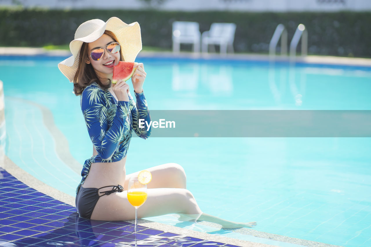 Portrait of young woman eating watermelon by drink in glass while sitting in swimming pool