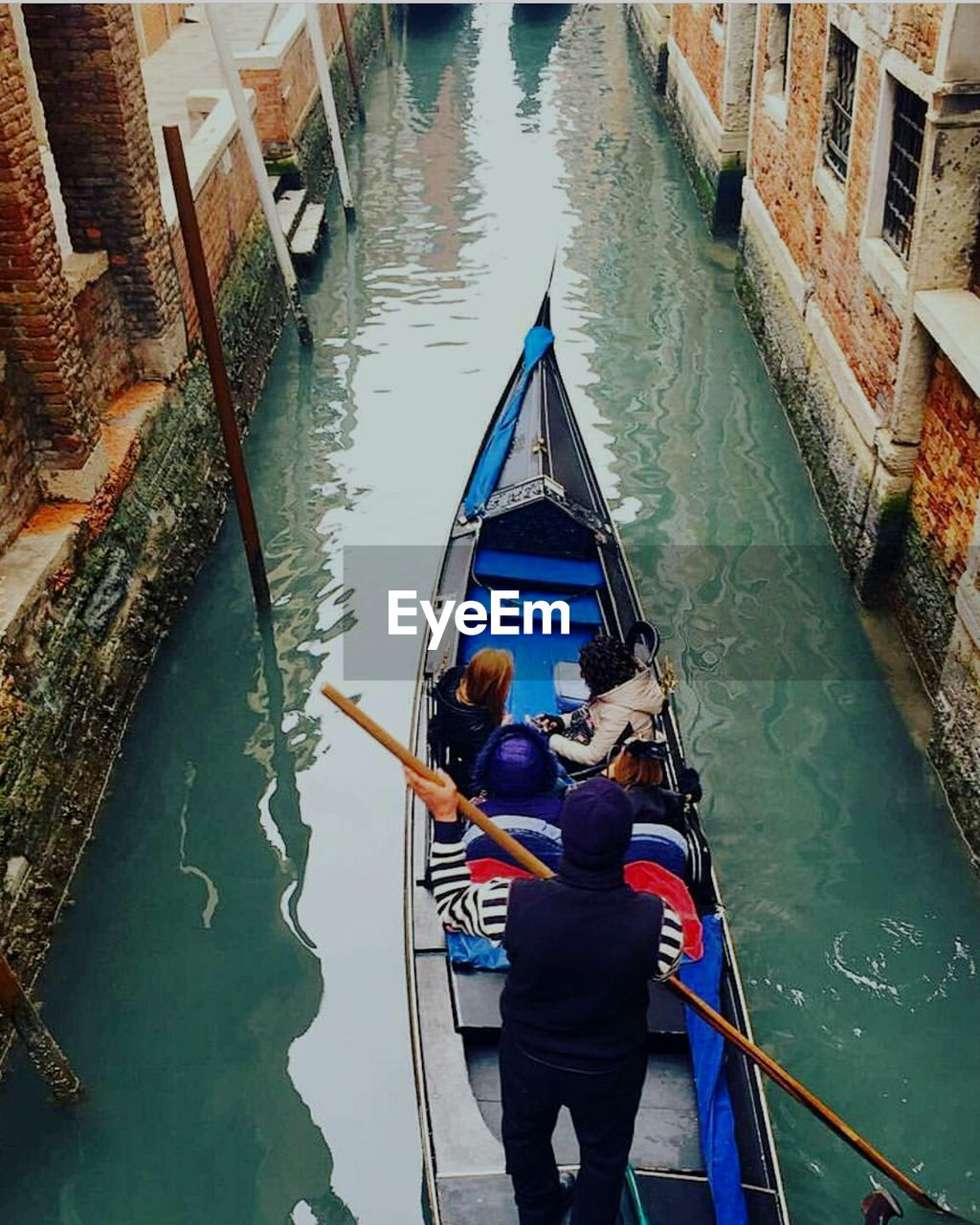 gondola - traditional boat, canal, high angle view, nautical vessel, gondolier, real people, water, gondola, transportation, rear view, men, oar, rowing, day, architecture, standing, outdoors, togetherness, two people, women, travel destinations, built structure, full length, building exterior, nature, adult, people